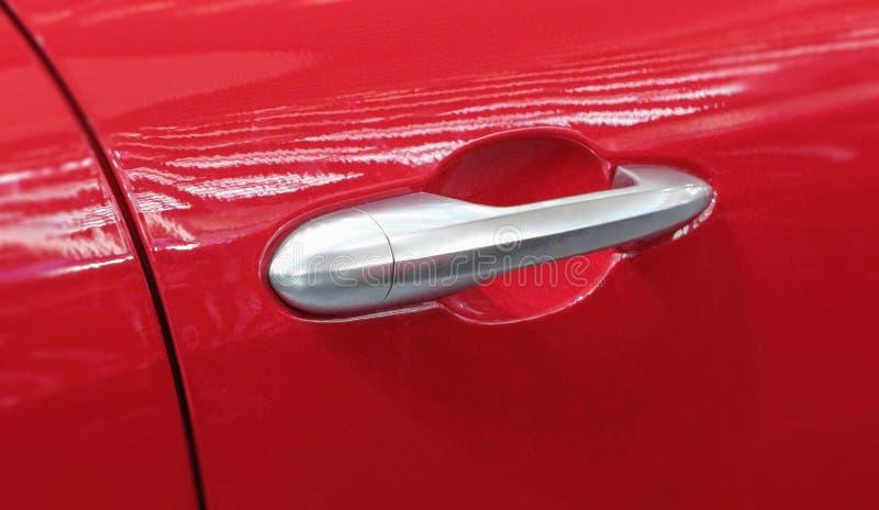El cierre para arriba del tirador de puerta gris del coche en el fondo rojo foto de archivo