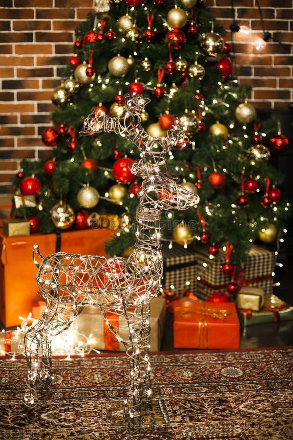 El ciervo hermoso de la Navidad con brillar intensamente se enciende en la noche en sala de estar con el árbol de navidad adornad imágenes de archivo libres de regalías