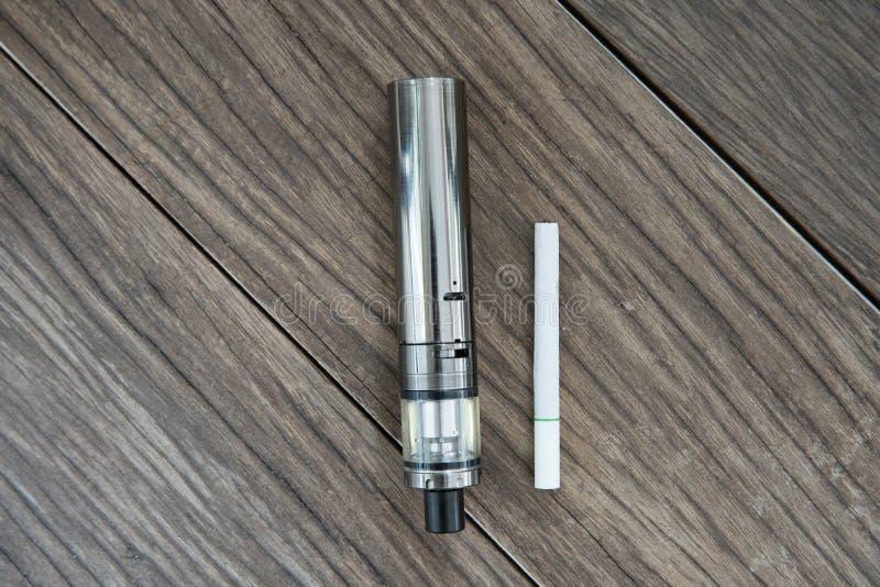 El cigarrillo electrónico con los cigarrillos regulares foto de archivo