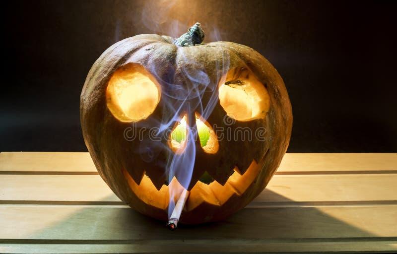 El cigarrillo que fuma en calabaza va a Halloween foto de archivo