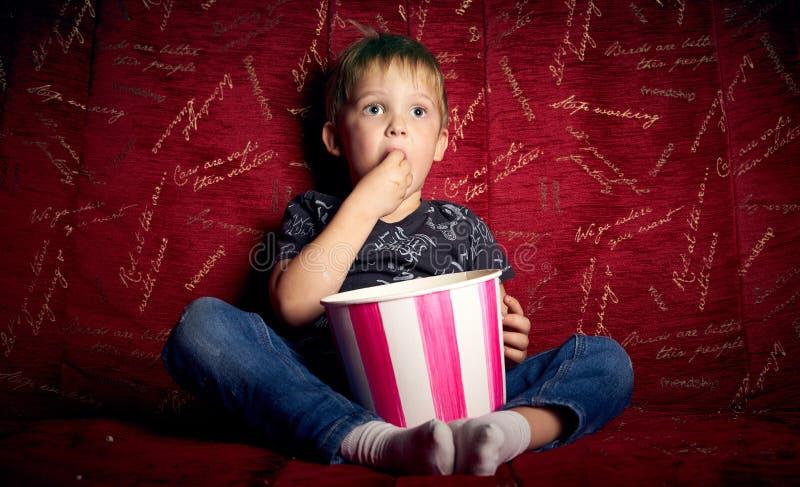 El cine de los niños: Un niño pequeño, preescolar, mira una película en casa en un sofá rojo grande y come las palomitas de un gr imagenes de archivo
