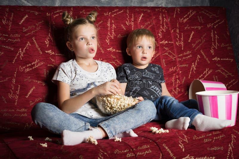 El cine de los niños: Una muchacha y un muchacho miran una película en casa en un sofá rojo grande en la oscuridad y comen las pa foto de archivo