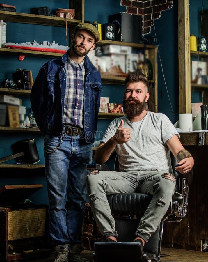 El cliente barbudo del inconformista se sienta en silla de los peluqueros y muestra el pulgar para arriba Cliente satisfecho con  imágenes de archivo libres de regalías