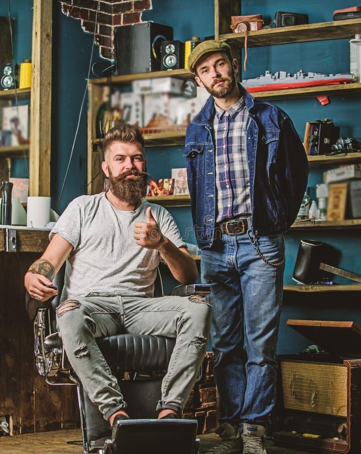 El cliente barbudo del inconformista se sienta en silla de los peluqueros y muestra el pulgar para arriba Cliente satisfecho con  imagen de archivo