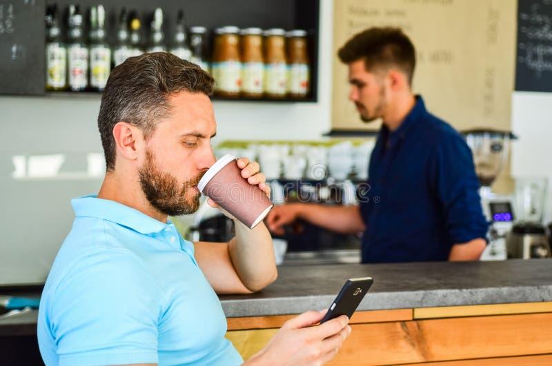 El cliente consiguió su bebida Tenga sorbo de energía El cliente del hombre con la barba goza del café en la taza de papel Bebida imagen de archivo libre de regalías