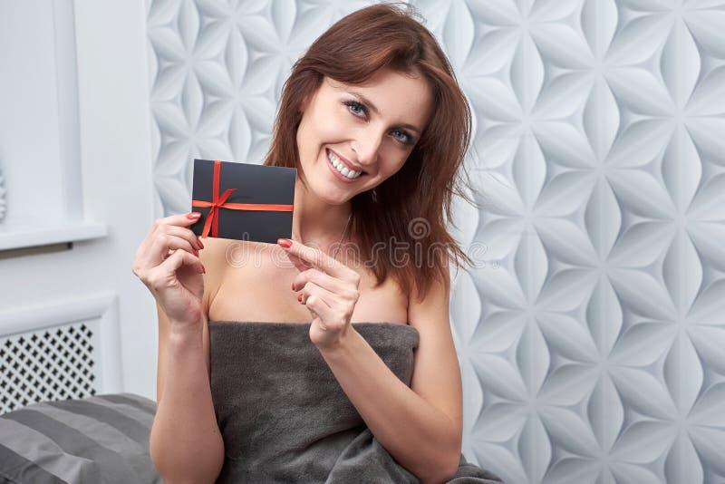 El cliente de la clínica de la cosmetología muestra un carte cadeaux imágenes de archivo libres de regalías