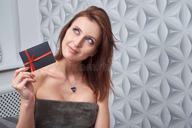 El cliente de la clínica de la cosmetología muestra un carte cadeaux fotos de archivo