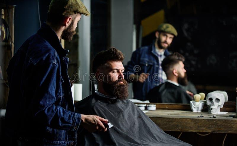 El cliente del inconformista consiguió nuevo corte de pelo Peluquero con las podadoras de pelo que miran el espejo, fondo de la b imagen de archivo libre de regalías