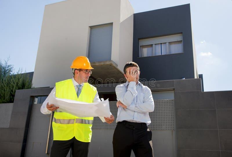 El cliente descontento en la tensión y el trabajador del capataz del constructor con el casco y el chaleco que discuten al aire l fotos de archivo libres de regalías