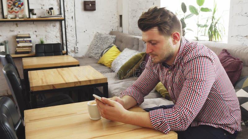 El cliente está utilizando su teléfono mientras que bebe el café fotos de archivo