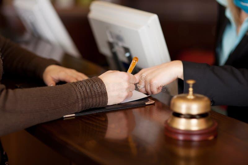 El cliente femenino de ayuda del recepcionista en el relleno encima del formulario imágenes de archivo libres de regalías