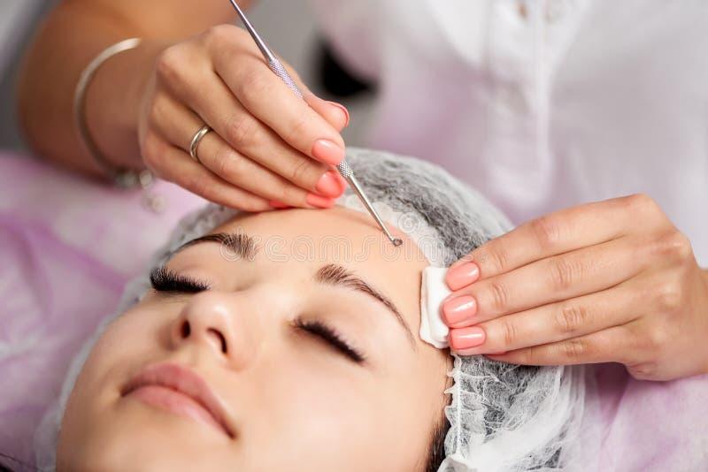 El cliente femenino está teniendo tratamiento facial con la ayuda de lazo del ojo fotos de archivo