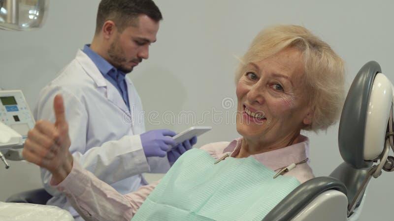 El cliente femenino muestra su pulgar para arriba en la silla dental imagen de archivo