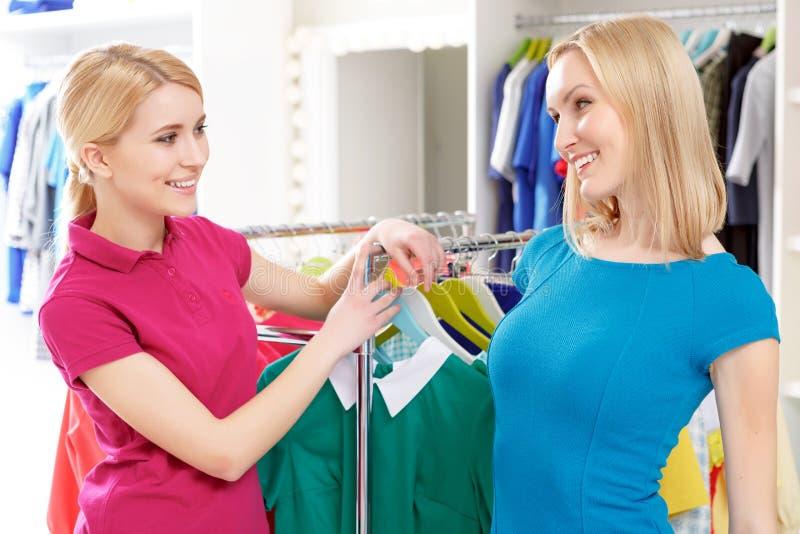 El cliente habla con el consultor de las ventas por la ropa fotografía de archivo