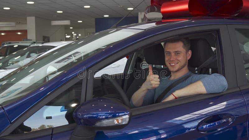 El cliente masculino muestra su pulgar para arriba por dentro del coche foto de archivo