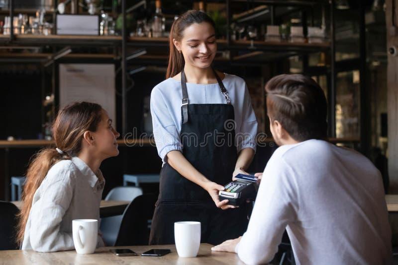 El cliente paga con tarjeta de crédito sin contacto, atractivo mesero con lector fotografía de archivo