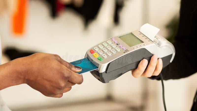 El cliente paga la ropa con tarjeta de crédito en una tienda de diseño foto de archivo libre de regalías