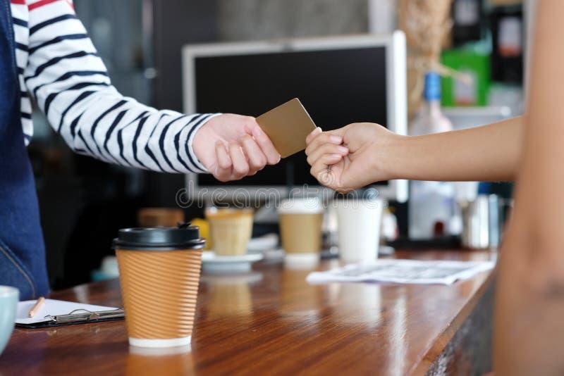 El cliente que paga el café por crédito, carga la tarjeta electrónica en el café fotografía de archivo libre de regalías