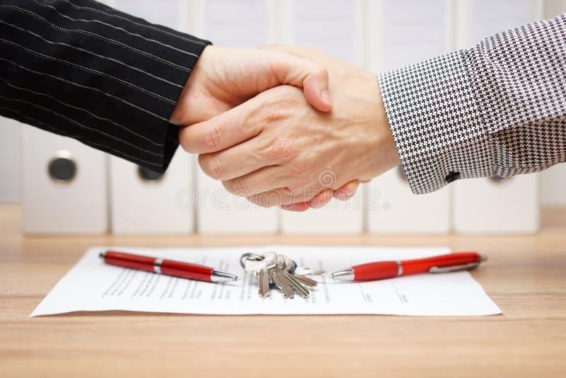 El cliente y el agente son apretón de manos sobre contrato de las propiedades inmobiliarias y k imágenes de archivo libres de regalías