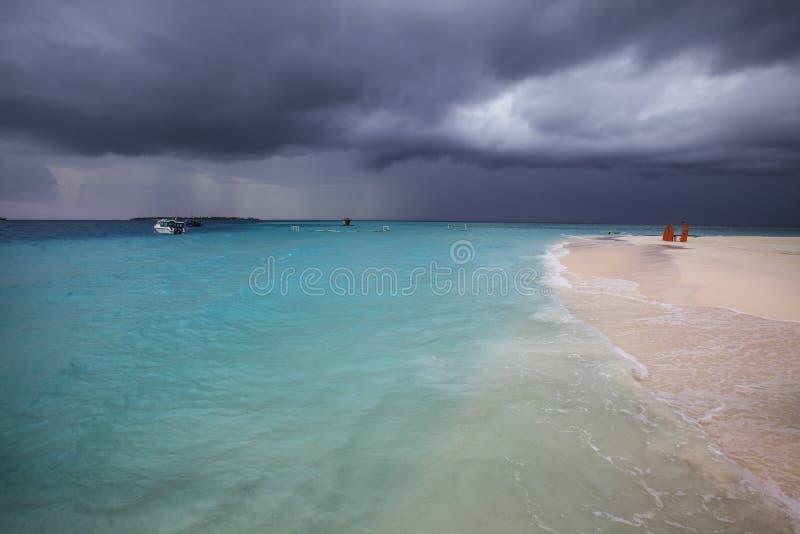 El clima tempestuoso, tormenta está viniendo a la playa maldiva foto de archivo