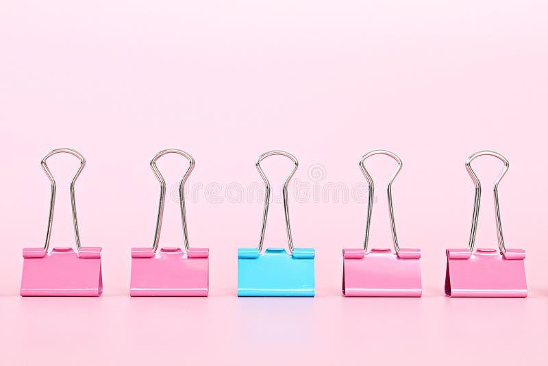 El clip azul de la carpeta que se coloca fuera de carpeta rosada acorta en fondo rosado con el espacio de la copia imágenes de archivo libres de regalías