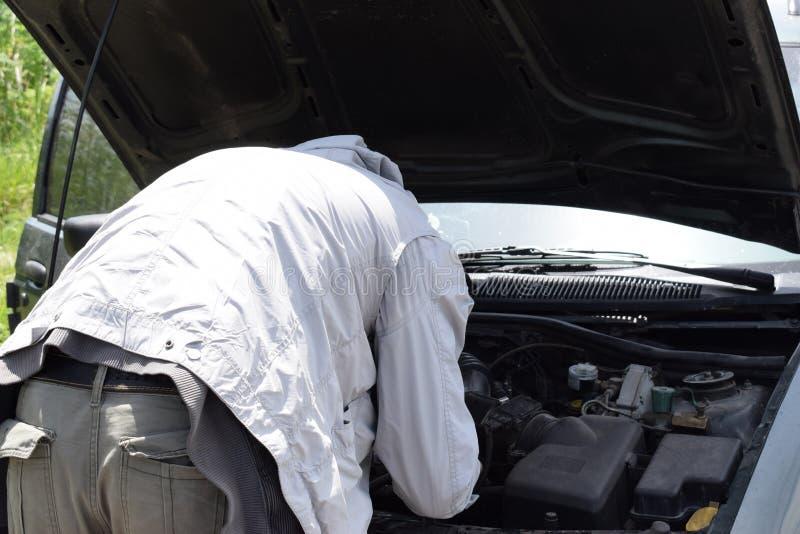 El coche analizado en el camino y un hombre mira qué se ha roto, un coche quebrado con una capilla abierta se coloca en el camino fotos de archivo libres de regalías