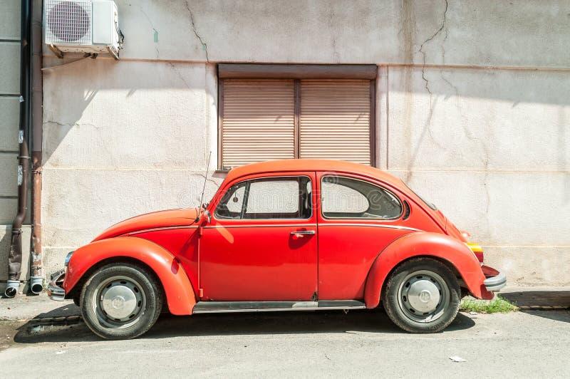 El coche anaranjado de VW Volkswagen Beetle de la obra clásica parqueó en la calle imagenes de archivo
