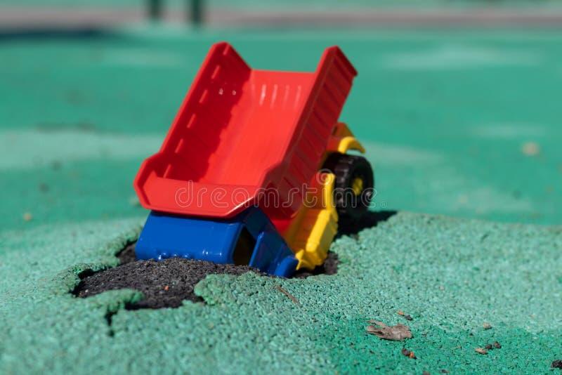 El coche cayó en el hoyo El camión plástico del juguete con un cuerpo rojo tenía un accidente Agujero en Asphalt Coating El a imagen de archivo libre de regalías
