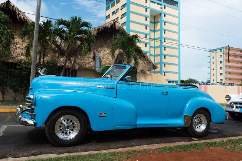 El coche clásico americano azul de Cuba parqueó el frente de un edificio fotos de archivo
