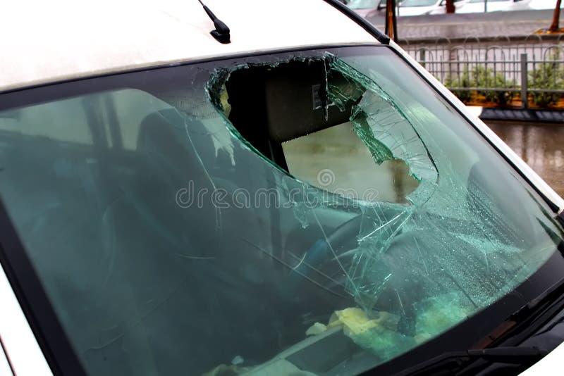 El coche con un parabrisas quebrado consigue mojado en el camino bajo la lluvia E imagen de archivo