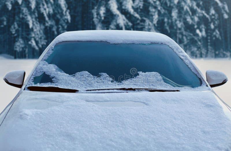 El coche congelado del invierno cubrió nieve, el parabrisas de la ventana delantera de la visión y la capilla en bosque nevoso imagen de archivo