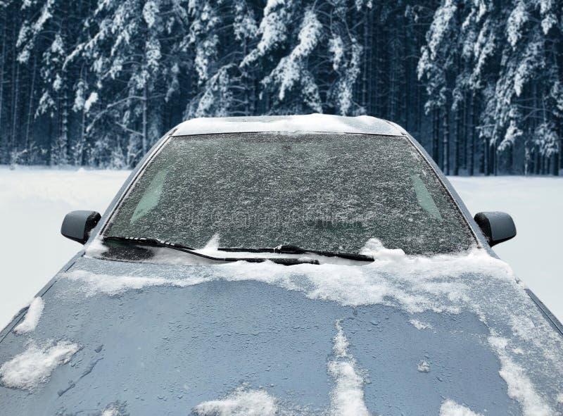 El coche congelado del invierno cubrió nieve, el parabrisas de la ventana delantera de la visión y la capilla en nevoso imagenes de archivo