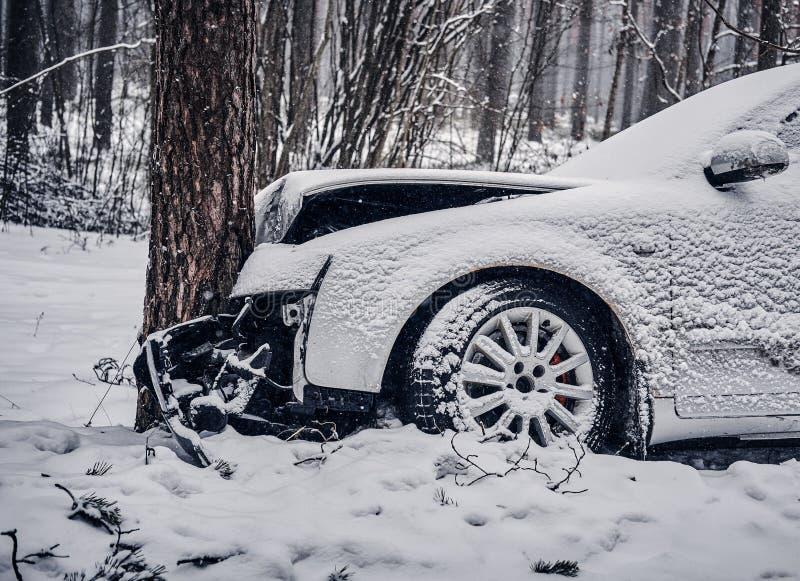 El coche consiguió en una resbalón y se estrelló en un árbol en un camino nevoso imagen de archivo
