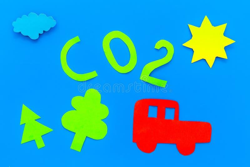 El coche contamina el ambiente por el dióxido de carbono Coche, ambiente y recorte del CO2 en la opinión superior del fondo azul imagenes de archivo