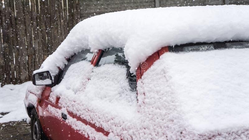 El coche, cubierto con la capa gruesa de nieve Consecuencia negativa de nevadas pesadas Coches estacionados fotos de archivo libres de regalías