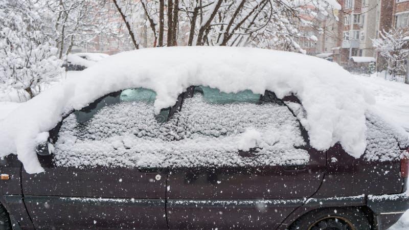 El coche, cubierto con la capa gruesa de nieve Consecuencia negativa de nevadas pesadas Coches estacionados imagenes de archivo