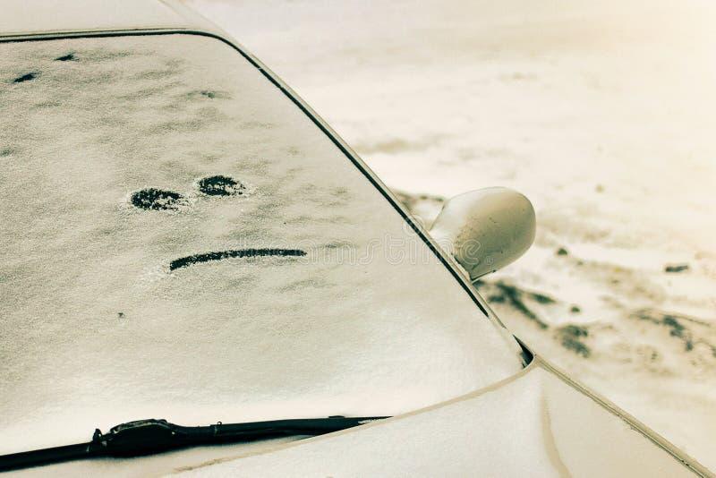 El coche cubrió con nieve con una cara malvada sobre el vidrio Paisaje del invierno fotografía de archivo