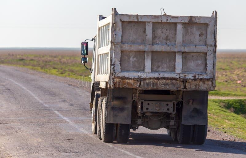 El coche de carga monta en una carretera de asfalto en la estepa imagen de archivo