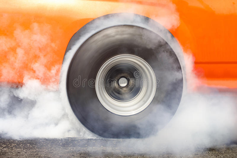 El coche de competición de la fricción quema el caucho de sus neumáticos fotos de archivo