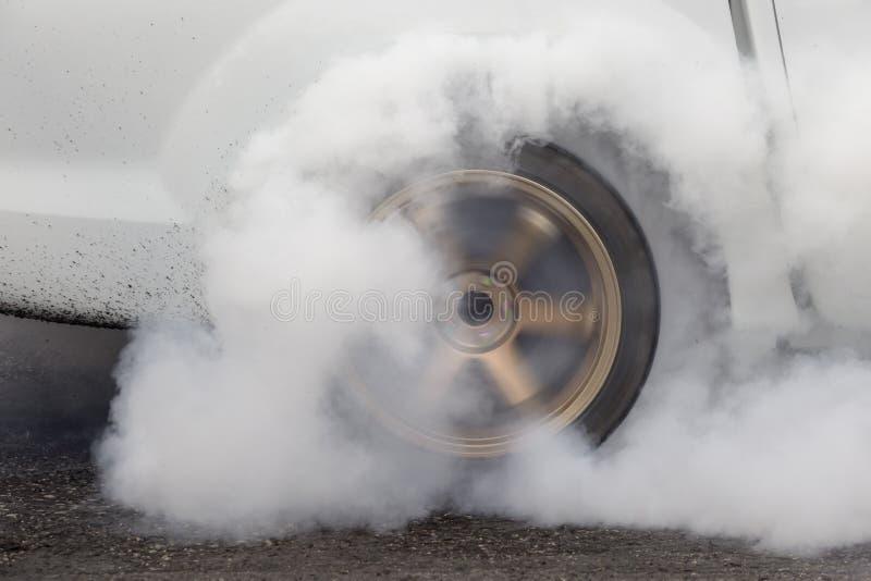 El coche de competición de la fricción quema el caucho de sus neumáticos imagen de archivo libre de regalías