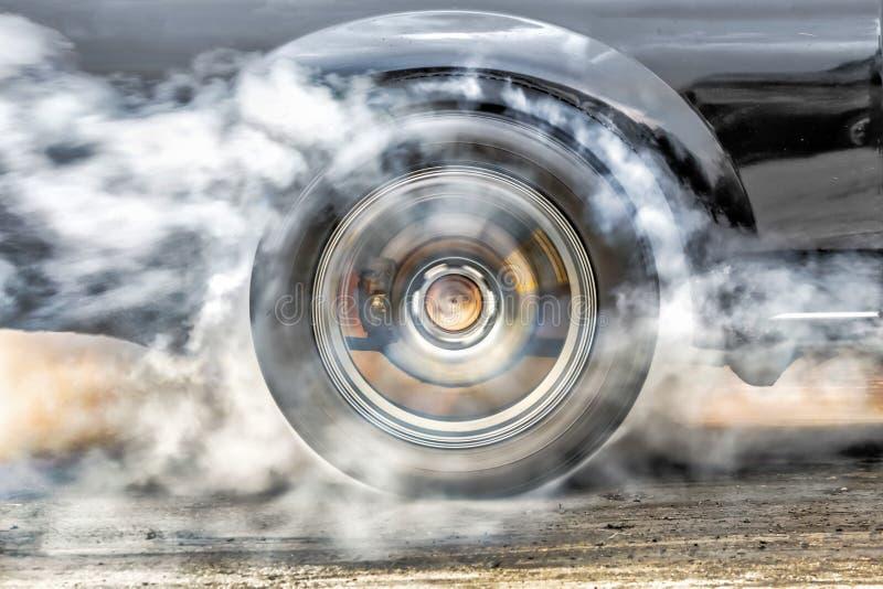 El coche de competición de la fricción quema los neumáticos en la línea del comienzo fotos de archivo