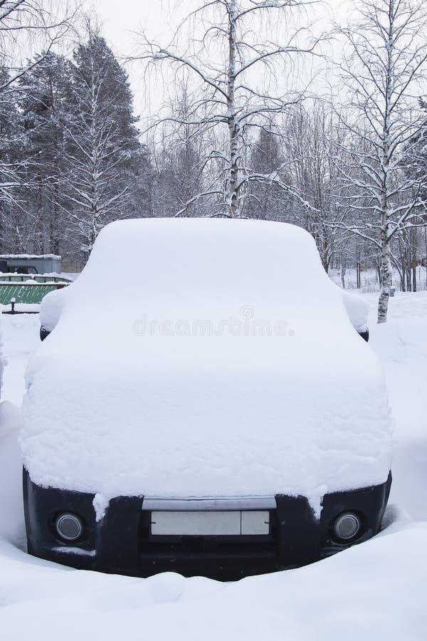 El coche debajo de una nieve acumulada por la ventisca de la nieve imagen de archivo libre de regalías