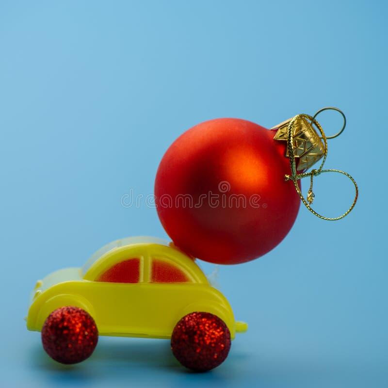 El coche del juguete lleva una bola roja del árbol de navidad imagen de archivo libre de regalías