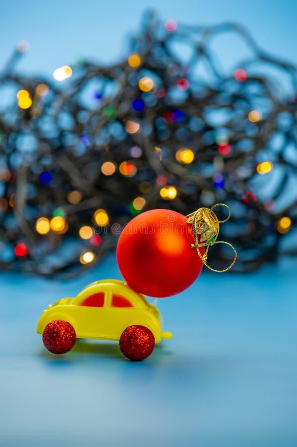 El coche del juguete lleva una bola roja del árbol de navidad imagenes de archivo