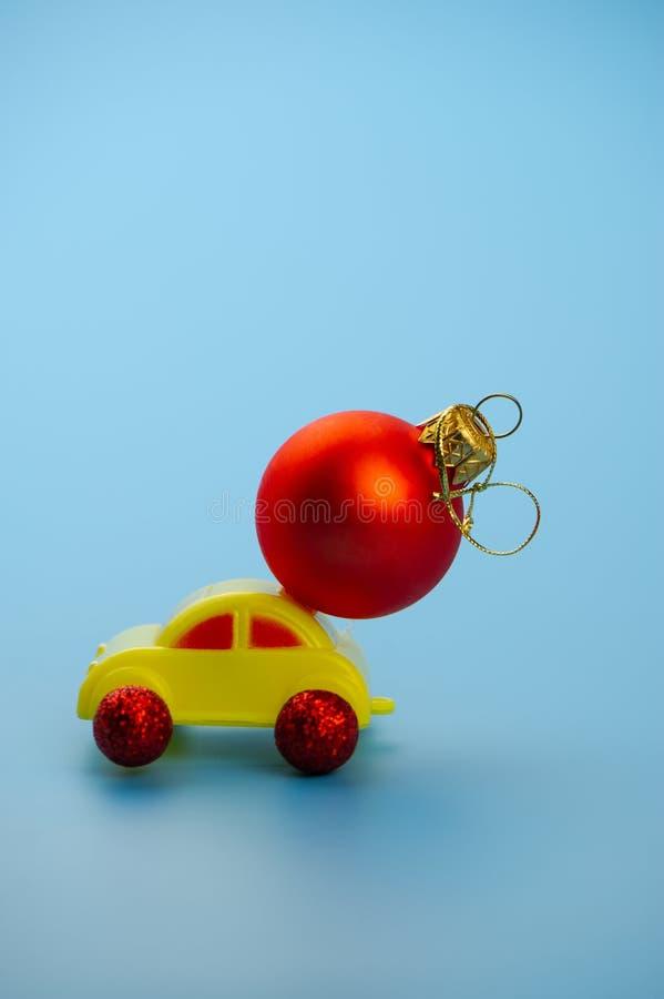 El coche del juguete lleva una bola roja del árbol de navidad foto de archivo libre de regalías