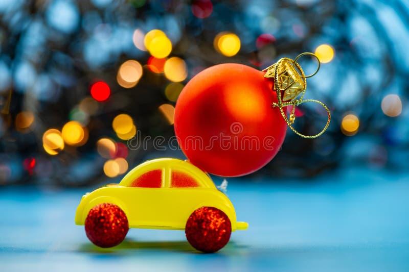 El coche del juguete lleva una bola roja del árbol de navidad imágenes de archivo libres de regalías