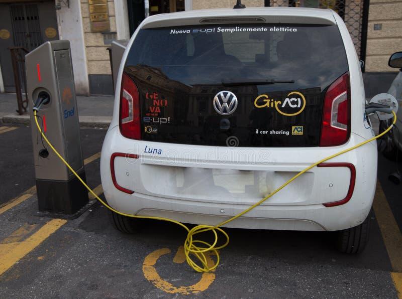 El coche eléctrico híbrido enchufable del e-Up de Volkswagen hace una pausa la estación de carga, en Génova, Italia imagenes de archivo