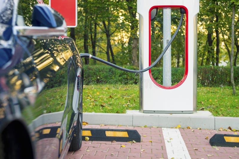 El coche eléctrico moderno tapó a la estación de carga en un estacionamiento imagen de archivo