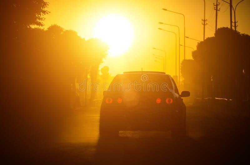 El coche en la carretera del camino monta contra el fondo de la puesta del sol imagen de archivo