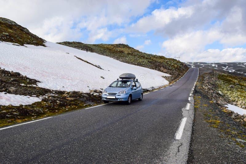 El coche en la carretera nacional de nieve turística Aurlandsvegen, Noruega foto de archivo libre de regalías